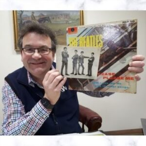 A Beatles photograph signed by John, Paul, George and Ringo during a break in filming at a Birmingham television studio. The photo will go under the hammer as Lot 372 in Richard Winterton Auctioneers' Antiques & Home Sale on Monday, April 12. Pictured is auctioneer Richard Winterton with the rare autographed photo and a copy of The Beatles' first LP Please Please Me.