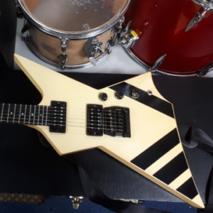 A 1985 Gibson Custom Shop XPL Explorer guitar with a cream finish, black detailing, Kahler floating tremolo and two Seymour Duncan humbucking pickups.