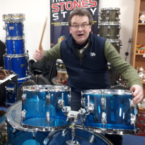Auctioneer Richard Winterton tries his hand at the drums behind a Ludwig Vistalite kit similar to one used by iconic Led Zeppelin drummer John Bonham.