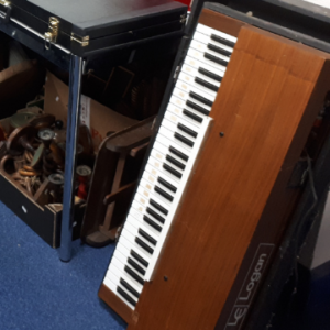A Logan Electronic Piano String Synthesizer in a teak veneered case and housed in a black Tolex covered case for protection. Made between 1972 and 1983 in Italy, this example's serial number 9729 identifies it as a pretty early one in lovely condition.